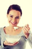 Young casual woman eating a yoghurt. — Stock Photo