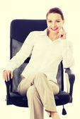 Beautiful business woman, boss sitting on a chair. — Stock Photo