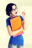 Student woman with coloured note pad pointing up. — Stock Photo