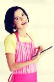 Young woman in pink apron using tablet computer — Stock Photo