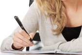 Hand writes with a pen in a notebook — Stock Photo