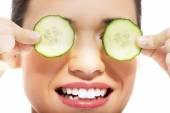 Beautiful woman receiving facial mask of cucumber — Stock Photo