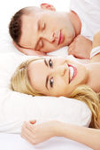 Young adult couple sleeping on the bed — Stock Photo