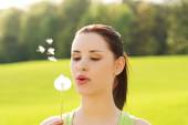 Woman blowing on a dandelion — Stock Photo