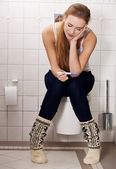 Woman sitting on a toilet — Stock Photo