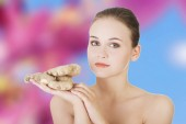 Young woman eating ginger — Stock Photo