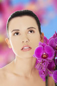 Beautiful woman with an orchid flower — Stock fotografie