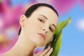 Woman with artistic make up and bamboo leaf — Stock Photo