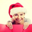 Beautiful woman wearing santa hat, holding shopping bag. — Stock Photo #58550335