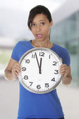 Happy young woman holding clock — Stok fotoğraf