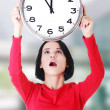 Shocked woman holding office clock — Stock Photo #58615771