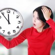 Shocked woman holding office clock — Stock Photo #58615825