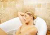 Relaxing woman propping up on bath by elbow — Stock Photo