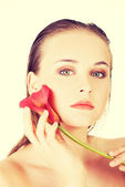 Beauty face of the young beautiful woman with flower. — Stock Photo