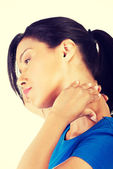 Young woman holding hand on her neck. — Stock Photo