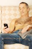 Mature man on a sofa looking at his smartphone — Stock Photo