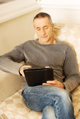 Mature man using digital tablet at home — Stock Photo