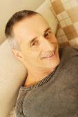 Mature man lying on the sofa — Stockfoto
