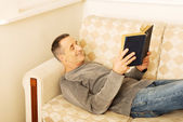 Mature man reading a book at home — ストック写真