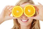 若い女性の目にオレンジを保持 — ストック写真