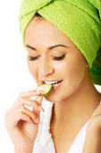 Portrait of woman in bathrobe eating cucumber — Stock Photo