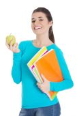 Happy woman holding an apple and notebooks — Stok fotoğraf