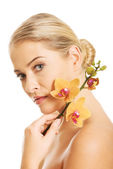 Beautiful nude woman with orange orchid flower — Stock Photo