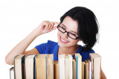 Happy woman searching for an interesting book — Stock Photo