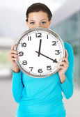 Happy woman holding office clock — Stock Photo