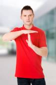 Handsome man showing time out sign — Stock Photo