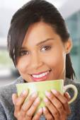 Young woman drinking something from big mug — Stock Photo
