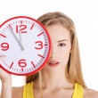 Attractive young woman holding a clock. — Stock Photo #62002353