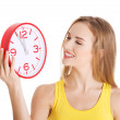 Attractive young woman holding a clock. — Stock Photo #62002371