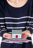 Woman with house model and euro bills — Stock Photo