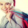 Beautiful woman in santa hat with shopping bags. — Stock Photo #62597025