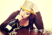 Drunk woman by a table with empty bottle. — Stockfoto