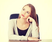 Beautiful casual woman sitting by a desk. — Stock Photo