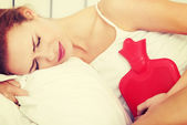Caucasian woman lying with hot water bag. — Stock Photo