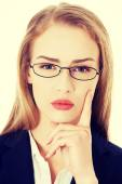 Business woman in eyeglasses with finger on cheek. — Stock Photo