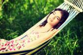 Young woman in dress relaxing in a hammock. — Stock Photo
