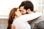 Happy beautiful couple kissing in the kitchen. — Stock Photo