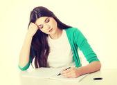 Casual woman writing in workbook. — Stock Photo