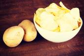 Potatoe chips in a bowl and potatoes. — Stock Photo