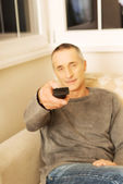 Mature man with remote control — Stockfoto
