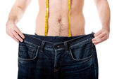 Man with oversized jeans and measure tape. — Stock Photo