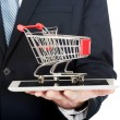 Businessman holding shopping cart on tablet — Stock Photo #66947725