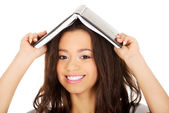 Student woman with a book on head. — Stock Photo