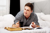 Happy man with a books in his bed. — Foto Stock