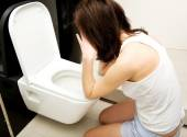 Woman vomiting in toilet. — Stock Photo