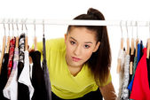 Young woman with clothes on hanger. — Stock Photo